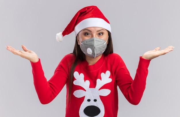 Zaskoczona młoda azjatycka dziewczyna ubrana w świąteczny kapelusz ze swetrem i maską medyczną, rozkładając ręce na białym tle