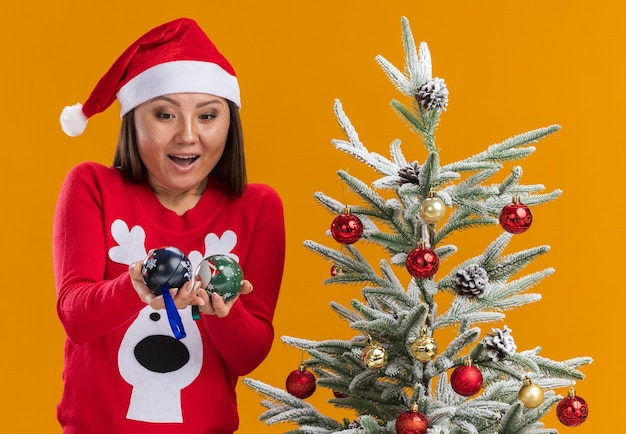Zaskoczona młoda azjatycka dziewczyna ubrana w świąteczny kapelusz ze swetrem stojąca w pobliżu choinki trzymając i patrząc na kulki choinkowe odizolowane na pomarańczowej ścianie
