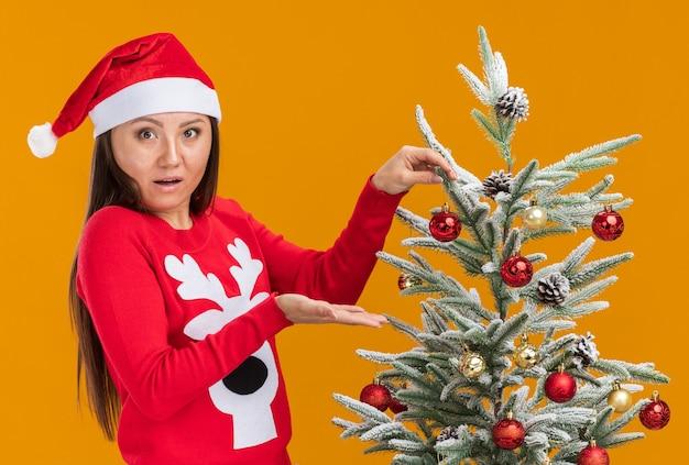 Zaskoczona młoda azjatycka dziewczyna ubrana w świąteczny kapelusz ze swetrem udekoruje choinkę na pomarańczowej ścianie