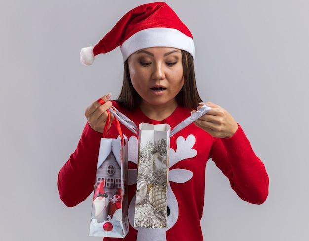 Zaskoczona młoda azjatycka dziewczyna w świątecznym kapeluszu z trzymającym sweter i patrząca na torbę z prezentami odizolowaną na białym tle