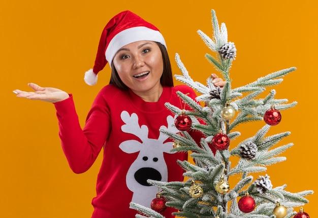 Zaskoczona młoda azjatykcia dziewczyna ubrana w świąteczny kapelusz ze swetrem stojący w pobliżu choinki, rozkładając rękę na białym tle na pomarańczowym tle