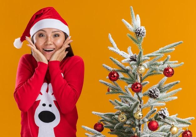 Zaskoczona młoda azjatykcia dziewczyna ubrana w świąteczny kapelusz ze swetrem stojący w pobliżu choinki zakryte usta rękami na białym tle na pomarańczowym tle