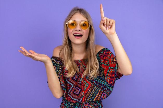 Zaskoczona młoda blond słowiańska dziewczyna w okularach przeciwsłonecznych trzymająca rękę otwartą i skierowaną w górę