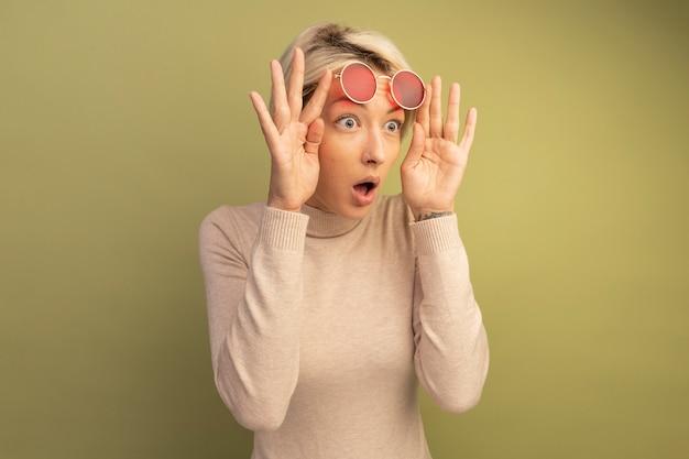 Zaskoczona młoda blondynka podnosząca okulary przeciwsłoneczne, patrząc z boku