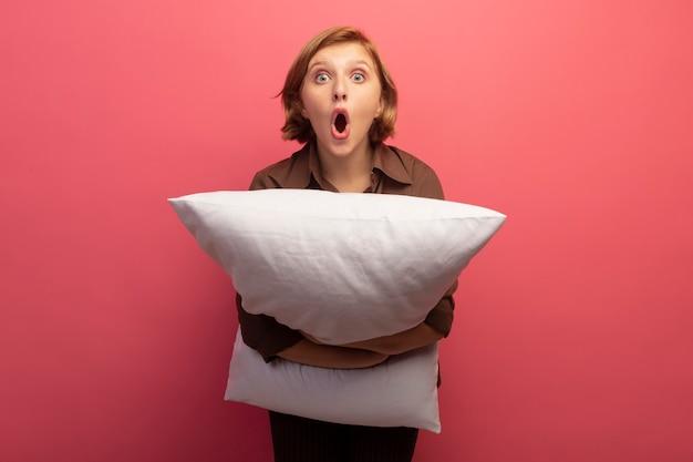Zaskoczona młoda blondynka przytula poduszkę patrząc na przód na różowej ścianie z miejscem na kopię