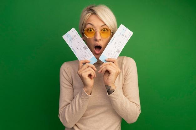 Zaskoczona młoda blondynka w okularach przeciwsłonecznych trzymająca bilety lotnicze w pobliżu twarzy odizolowanej na zielonej ścianie z miejscem na kopię