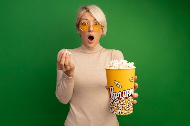 Zaskoczona młoda blondynka w okularach przeciwsłonecznych trzymająca wiadro popcornu i kawałki popcornu