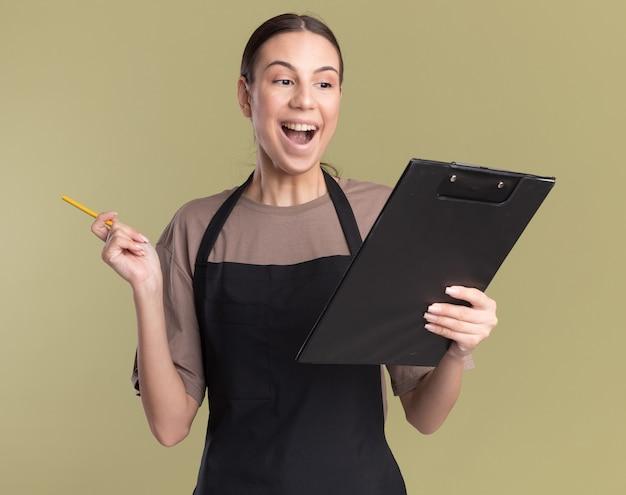 Zaskoczona młoda brunetka fryzjerka w mundurze trzyma ołówek i schowek