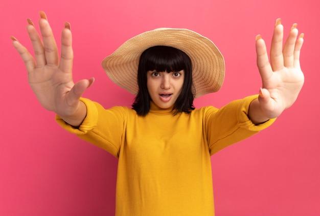 Zaskoczona młoda brunetka kaukaska dziewczyna w kapeluszu plażowym wyciągając ręce