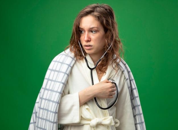 Zaskoczona młoda chora dziewczyna, patrząc na bok w białej szacie owiniętej w kratę, słuchająca własnego bicia serca odizolowanego na zielono