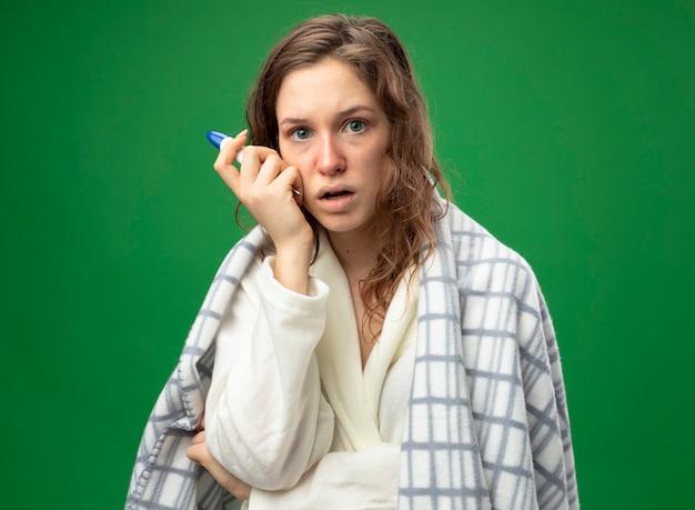 Zaskoczona, młoda chora dziewczyna ubrana w białą szatę zawiniętą w kratę, trzymając termometr i kładąc dłoń na policzku na białym tle