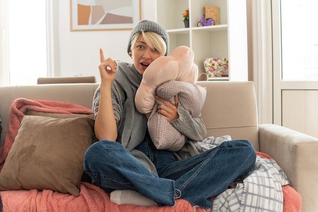Zaskoczona młoda, chora słowiańska kobieta z szalikiem na szyi w zimowej czapce trzymająca poduszkę i wskazująca w górę, siedząca na kanapie w salonie