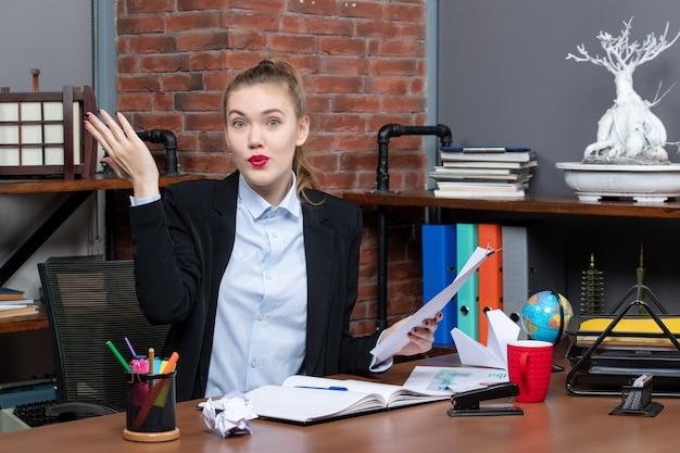 Zaskoczona młoda dama siedzi przy stole i trzyma dokument, pytając kogoś w biurze
