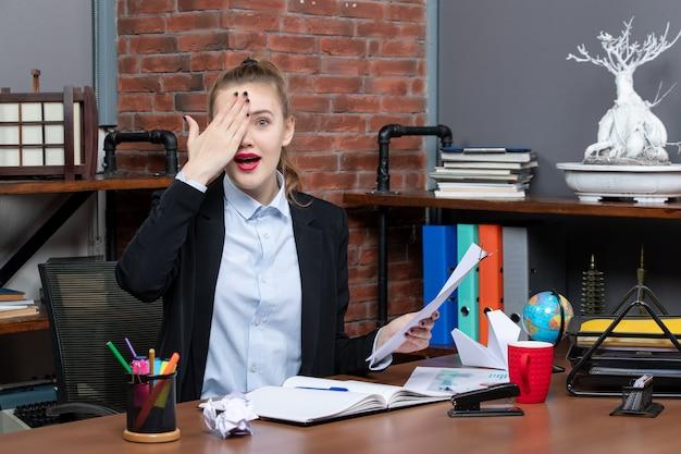 Zaskoczona młoda dama siedzi przy stole i trzyma w biurze dokument zakrywający połowę jej twarzy