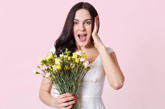 Zaskoczona młoda dama stoi pod różowym różem, szeroko zdziwiona otwiera usta i trzyma bukiet wiosennych kwiatów