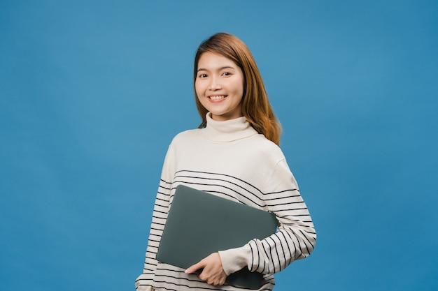 Zaskoczona młoda dama z azji trzyma laptopa z pozytywnym wyrazem twarzy, uśmiecha się szeroko, ubrana w codzienną odzież i patrzy na przód na niebieską ścianę