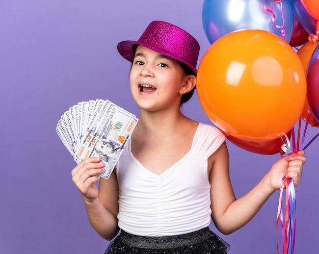 Zaskoczona młoda dziewczyna kaukaski z fioletowym kapeluszem strony, trzymając balony z helem i pieniądze na białym tle na fioletowej ścianie z miejsca na kopię