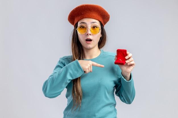 Zaskoczona młoda dziewczyna na walentynki w kapeluszu z okularami trzymająca i wskazująca na obrączkę na białym tle