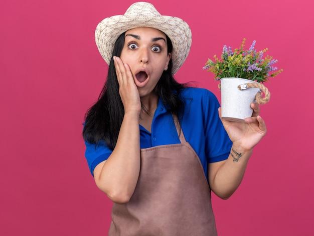 Zaskoczona młoda dziewczyna ogrodniczka w mundurze i kapeluszu trzymająca doniczkę, patrząca na przód, trzymająca dłoń na twarzy odizolowana na różowej ścianie