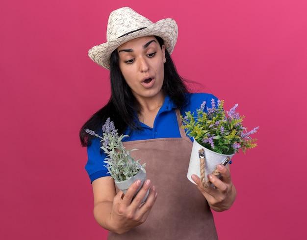 Zaskoczona młoda dziewczyna ogrodniczka w mundurze i kapeluszu, trzymająca i patrząca na doniczki izolowane na różowej ścianie