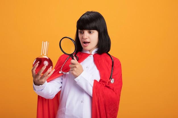 Zaskoczona młoda dziewczyna superbohatera w stetoskopie z szlafrokiem medycznym i płaszczem trzymająca i patrząc przez lupę na szklaną butelkę chemiczną wypełnioną czerwonym płynem