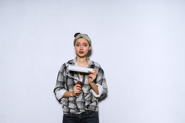 Zaskoczona młoda dziewczyna trzyma wałek do malowania ścian, naprawy repair
