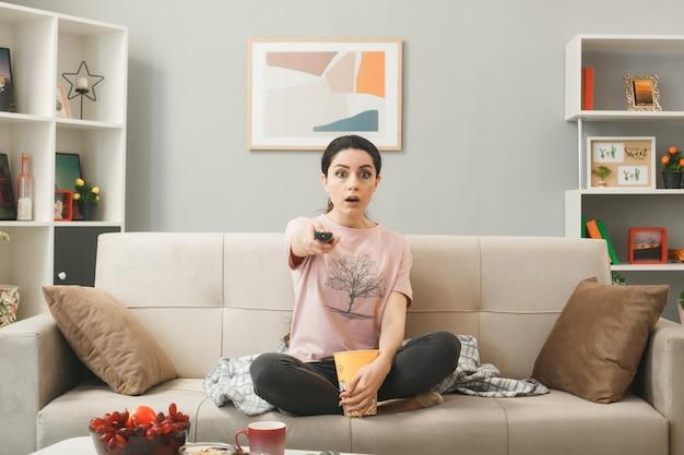 Zaskoczona młoda dziewczyna trzymająca pilota do telewizora, siedząca na kanapie za stolikiem kawowym w salonie