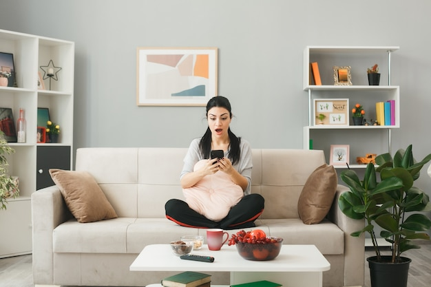 Zaskoczona młoda dziewczyna z poduszką siedzi na kanapie za stolikiem do kawy, trzymając i patrząc na telefon w salonie