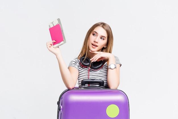Zaskoczona młoda dziewczyna z walizką i paszportem na białym tle na białej ścianie