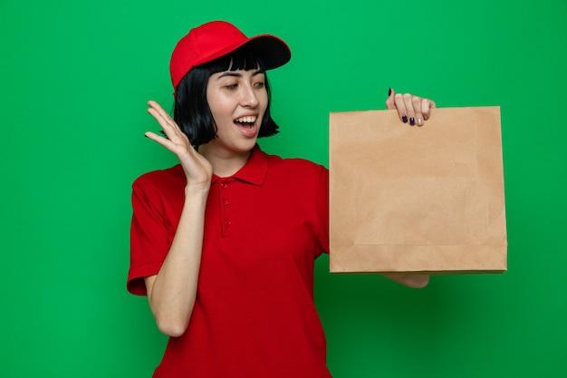 Zaskoczona młoda kaukaska dziewczyna dostarczająca jedzenie, trzymająca i patrząca na papierowe opakowanie żywności