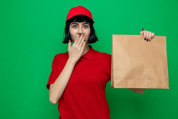Zaskoczona młoda kaukaska dziewczyna dostarczająca jedzenie trzymająca opakowanie z jedzeniem i kładąca rękę na ustach