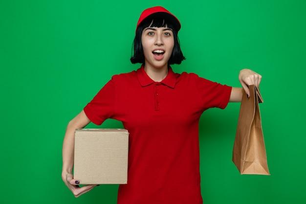 Zaskoczona młoda kaukaska dziewczyna dostarczająca jedzenie, trzymająca opakowanie żywności i kartonowe pudełko