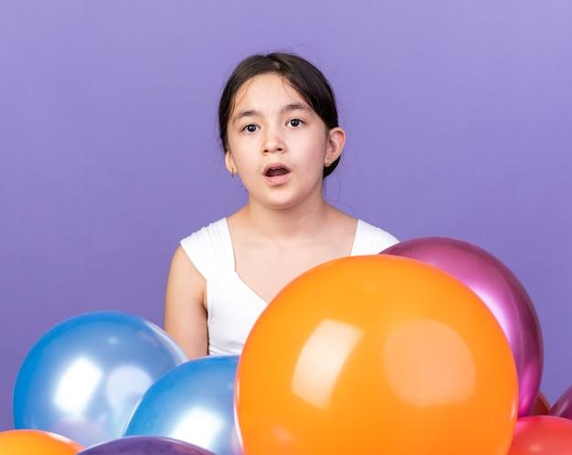Zaskoczona młoda kaukaska dziewczyna trzyma balony z helem odizolowane na fioletowej ścianie z miejscem na kopię
