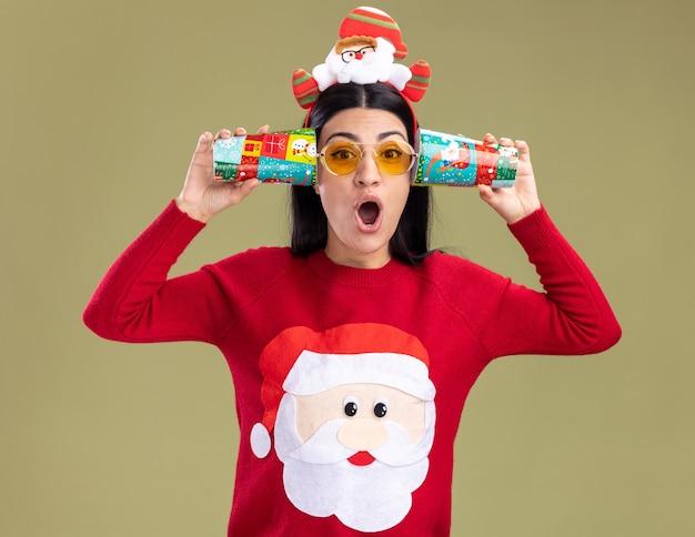 Zaskoczona młoda kaukaska dziewczyna ubrana w opaskę świętego mikołaja i sweter w okularach trzymająca plastikowe kubki przy uszach słuchając rozmów odizolowanych na oliwkowozielonej ścianie