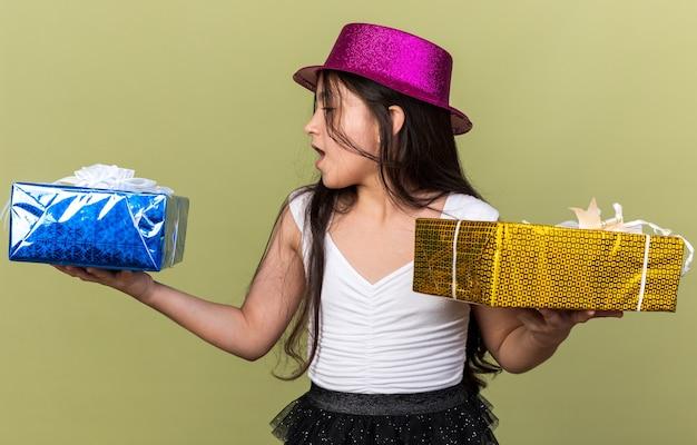 Zaskoczona młoda kaukaska dziewczyna w fioletowym kapeluszu imprezowym, patrząca na pudełko z prezentami, trzymająca każdą rękę odizolowaną na oliwkowozielonej ścianie z miejscem na kopię