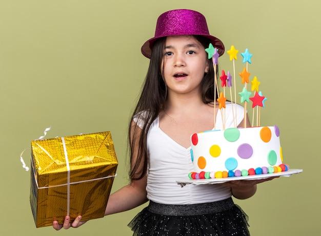 Zaskoczona młoda kaukaska dziewczyna w fioletowym kapeluszu, trzymająca tort urodzinowy i pudełko na prezent, odizolowane na oliwkowozielonej ścianie z miejscem na kopię