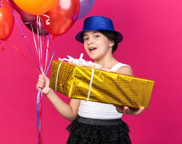 Zaskoczona młoda kaukaska dziewczyna w niebieskim kapeluszu imprezowym trzymająca pudełko i balony z helem odizolowane na różowej ścianie z miejscem na kopię