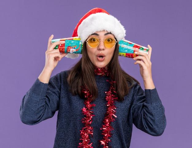 Zaskoczona młoda kaukaska dziewczyna w okularach przeciwsłonecznych z czapką mikołaja i girlandą na szyi trzyma papierowe kubki blisko uszu na fioletowym tle z miejscem na kopię