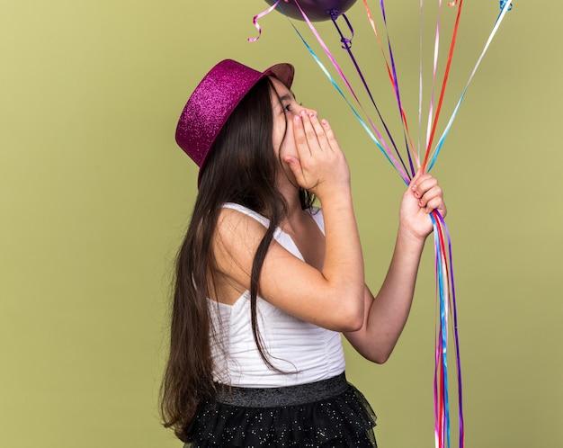 Zaskoczona młoda kaukaska dziewczyna z fioletowym kapeluszem imprezowym kładąca dłoń na twarzy, trzymając i patrząc na balony z helem odizolowane na oliwkowej ścianie z miejscem na kopię