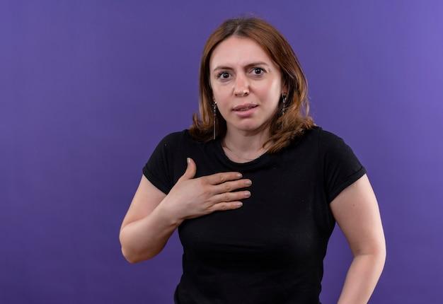 Zaskoczona młoda kobieta dorywczo kładzie rękę na klatce piersiowej na odosobnionej fioletowej ścianie z miejsca na kopię
