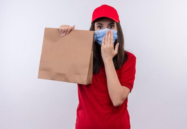 Zaskoczona młoda kobieta dostawy ubrana w czerwoną koszulkę w czerwonej czapce nosi maskę na twarzy trzymającą paczkę i kładzie dłoń na odizolowanej białej ścianie