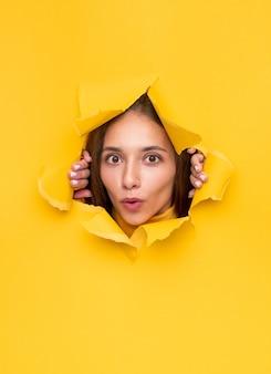 Zaskoczona młoda kobieta drze dziurę w żywym żółtym papierze i patrzy ze zdumieniem