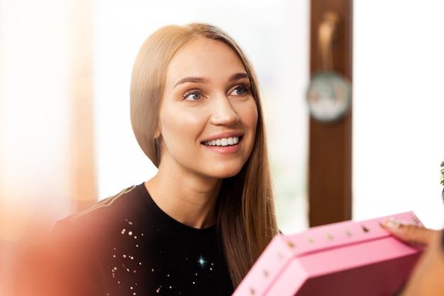 Zaskoczona młoda kobieta otwiera różowe pudełko z prezentem
