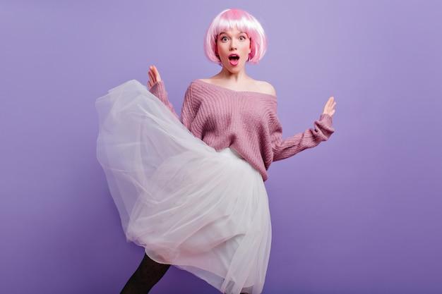 Zaskoczona młoda kobieta w bujnej białej spódnicy, pozowanie na fioletowej ścianie. modna modelka w kolorze różowym peruke wyrażająca zdumienie.