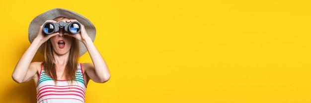 Zaskoczona młoda kobieta w kapeluszu i sukience w paski wygląda zdziwiona przez lornetkę na żółtym polu. transparent