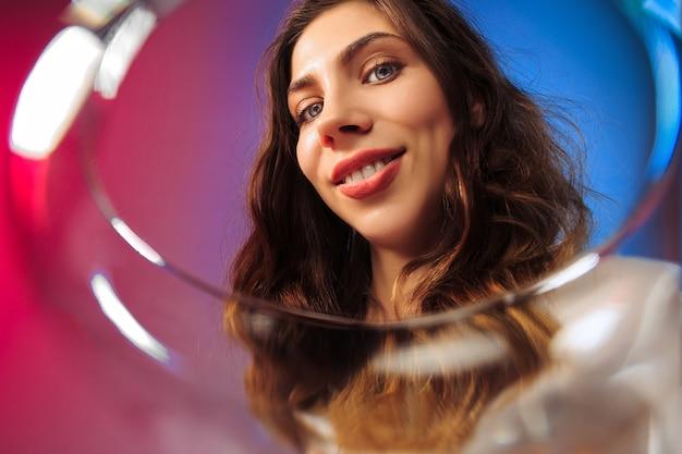 Zaskoczona młoda kobieta w strojach imprezowych pozuje przy lampce wina.