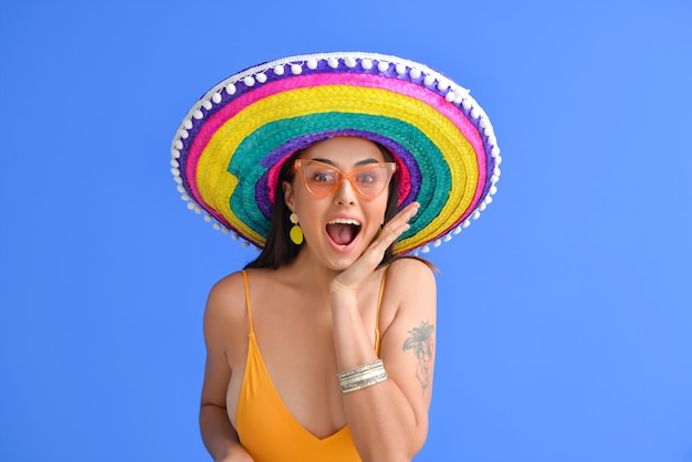 Zaskoczona młoda kobieta w stroju kąpielowym i kapeluszu sombrero na kolor