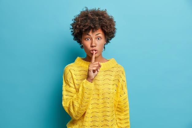 Zaskoczona młoda kobieta wykonuje gest uciszenia, prosząc o zachowanie informacji w tajemnicy, pokazuje, że znak ciszy ma zszokowany wyraz twarzy, nosi swobodny żółty sweter odizolowany na niebieskiej ścianie