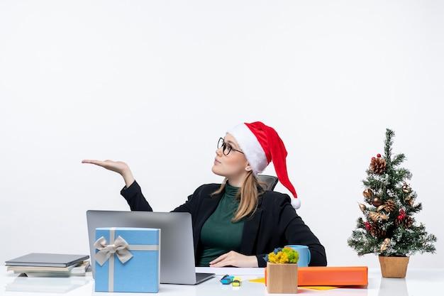 Zaskoczona młoda kobieta z czapką świętego mikołaja i okularami siedząca przy stole z choinką i prezentem na nim i wskazująca na prawą stronę na białym tle