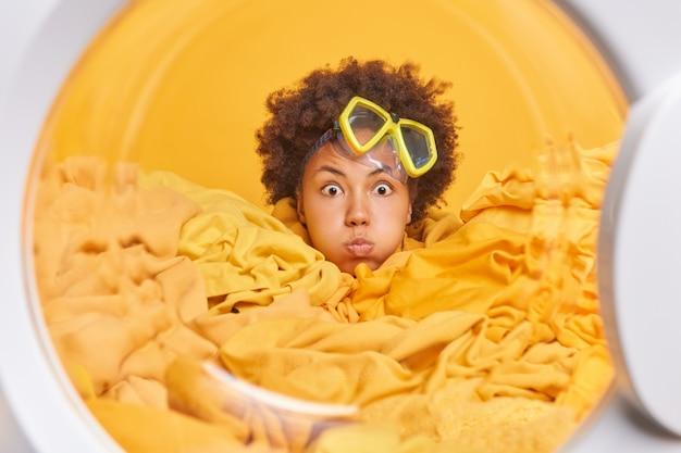Zaskoczona młoda kobieta z kręconymi włosami patrzy zszokowana na aparat utopiony w praniu